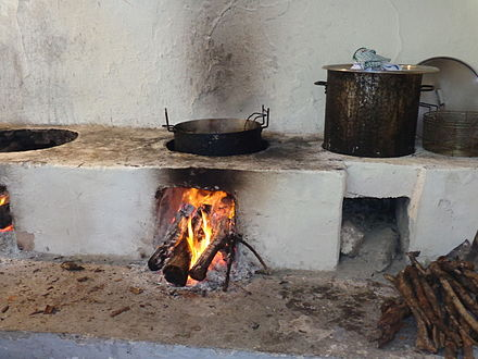 A wood-burning open-air cooking stove. Smoke from solid fuels like wood is a large source of PAHs globally. Kochen uber offenem Feuer.JPG