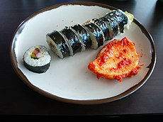 A sliced roll of Kimbap, with some kimchi.