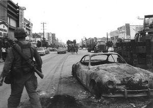 暴動後、燃やされた車の近くに立つアメリカ軍兵士。