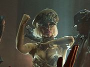 A blond woman wearing a khaki colored bustier and khaki cap with the word GAGA written on it. She looks towards the left of the image. Her left hand is folded in front of her and the right hand is gestured upwards. The silhouette of a male dancer is visible to her left.