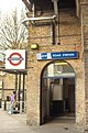 "A beige-bricked building with a dark-blue, rectangular sign reading ""LATIMER ROAD STATION"" in white letters all under a white sky"