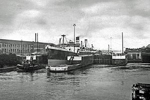 Latchford - Latchford Locks looking east as an ocean liner, with tugs, leaves for the Eastham end of the canal. Smaller lock at centre, and ship berth at right