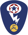 Oval shaped shoulder patch with a deep blue background. At the top is a red circle and blue star, the patch of the Army Service Forces. It is surrounded by a white oval, representing a mushroom cloud. Below it is a white lightning bolt cracking a yellow circle, representing an atom.