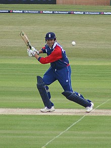 A man in a red and navy blue cricket uniform and helmet stands on a cricket pitch, watching the ball after hitting it to his left.
