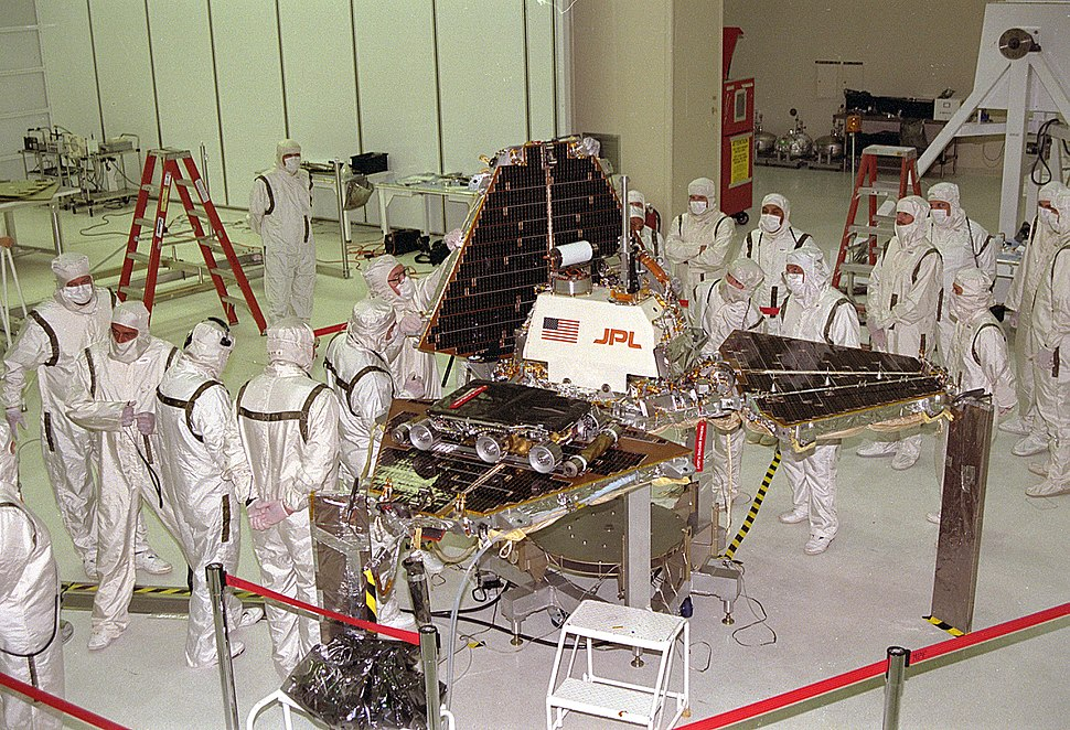 A group of scientists, all wearing white protective clothing, gather around a spacecraft as it's being folded into its launch position; a triangular pyramid shape.