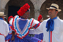A man and woman in colorful dress dancing