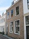 Huis met rechte gecementeerde gevel, op klossen rustende gootlijst