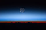 This image shows the Moon at the centre, with the limb of Earth near the bottom transitioning into the orange-colored troposphere. The troposphere ends abruptly at the tropopause, which appears in the image as the sharp boundary between the orange- and blue-colored atmosphere. The silvery-blue noctilucent clouds extend far above Earth's troposphere.