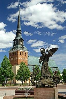 Mora kirke, set fra sydvest ved Mora gågade.   I forgrunden ses statuen forestillende Sankt Mikael og dragen.