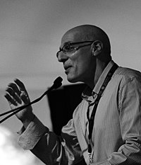 Black and white photograph of Gordon Korman, author of young adult fiction, speaking at the National Book Festival in September 2011. Photograph depicts Korman in profile view, facing left and speaking into a microphone. His right hand is raised to approximately shoulder height, palm facing the audience, with fingers slightly closed as if grasping an invisible ball.