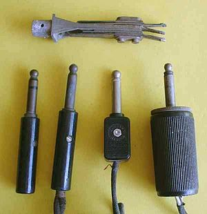 "Phone connector (audio) - Old-style male tip-sleeve (""pin"" or ""jack"") connectors. The leftmost plug has three conductors; the others have two. At the top is a three-conductor panel jack."
