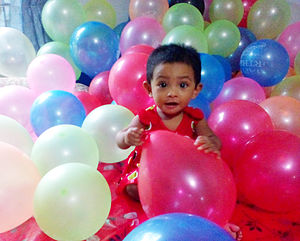 Birthday - A one-year-old girl playing with her birthday balloons in Bangladesh