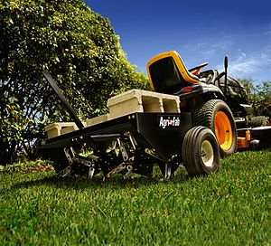English: Agri-Fab plug aerator towed by a lawn...