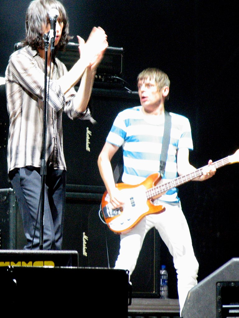 Two people (one vocalist and one guitarist) performing on stage
