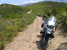 A BMW R1150GS parked on a gravel trail with scrub-covered mountains in the background