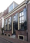 foto van Eenvoudig laag huis met rechte kroonlijst. Brede bakstenen gevel. Gevelsteen met de Franse lelie