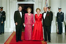 Ronald Reagan, Margaret Thatcher, Nancy Reagan and Denis Thatcher smile while standing on a red carpet leading to a large door. Men in US military dress stand in the background. Beside the door is a Union Jack flag.