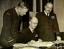 Three men in military uniforms, two standing and one seated, looking at papers on a desk