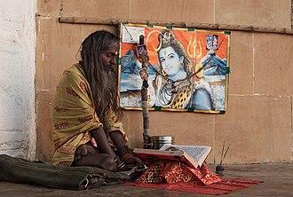 Sadhu - A sadhu in yoga position, reading a book in Varanasi