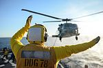 Sailor signals the pilot of an MH-60 Seahawk from the flight deck of USS Porter. (31067174400).jpg
