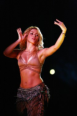 A woman with golden hair is striking a pose and waving her hands in the manner of a belly dancer. She is dressed in a flesh-toned bra and a brown fringe-adorned skirt.