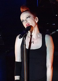 A light-skinned woman with red hair is seen looking up while she sings into her microphone