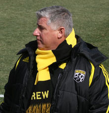 A portly man with graying hair. He is wearing a coat and scarf that are both black and yellow.