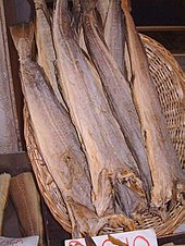 Photo of several dried fish suspended head-down