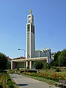 Une église moderne avec en son centre un impressionnant clocher parallélépipédique surmonté d'une croix d'or; le corps de l'édifice monte en escalier le long de la pente du terrain; de la pelouse et des fleurs au premier plan.
