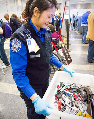 TSA officer carrying a bin of prohibited items that passengers have surrendered. TSA Officer Carrying Prohibited Items.png
