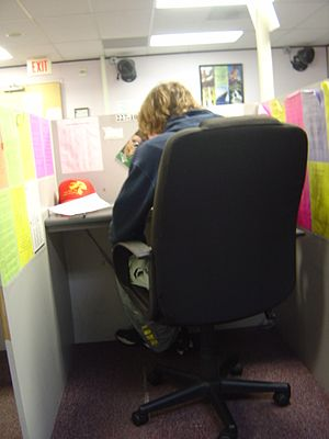 Telemarketing - Telemarketing agent sitting in a cubicle. The brightly colored rebuttal sheets are used to answer most questions a customer might have.