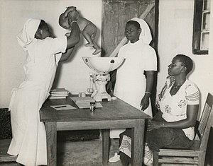 Midwife - Tanzanian midwife weighing an infant and giving advice to the mother