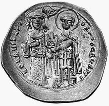 Round silver coin with two standing figures, the left one dressed in regalia and the right one as a warrior saint, handing a castle to the former