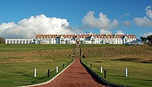 A golf course. In the background is the Turnberry Hotel, a two-story hotel with white façade and a red roof.