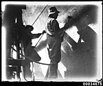 Two men scraping rust from the hull of a ship, possibly French warship BELLATRIX, 1930-1932 (7633462154).jpg
