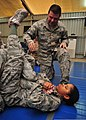 U.S. Air Force Master Sgt. Robert Reader, kneeling, with the 380th Air Expeditionary Wing, instructs Senior Airman Cherelle Doss, with the 380th Expeditionary Force Support Squadron, on performing an arm bar 140110-F-XR500-273.jpg