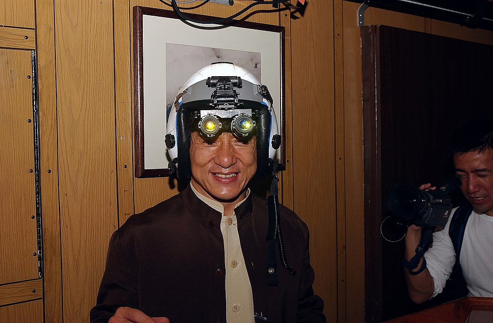 US Navy 021202-N-0271M-016 Jackie Chan tries on a fighter pilot's helmet with night vision goggles attached during his visit aboard USS Kitty Hawk