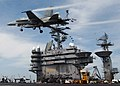 US Navy 040425-N-0905V-004 An F-A-18C Hornet flies past the island of USS Carl Vinson (CVN 70).jpg