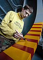 US Navy 040506-N-6653C-022 Aviation Boatswain's Mate 3rd Class Michael Ostrude, of Cortland, Ohio, paints part of the hangar bay door aboard USS George Washington (CVN 73).jpg
