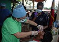 US Navy 070602-N-2296G-135 1st Lt. Jeanne Valdez-Lingan with the Philippines Navy (left), assisted by U.S. Navy Hospital Corpsman 2nd Class Crystal Ruff extract a tooth from a patient during a Dental Civic Action Project (DENTC.jpg