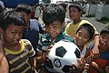 US Navy 070624-N-9421C-055 Children living at the Guinobatan Evacuation Center show off a new soccer ball given by Sailors from USS Peleliu (LHA 5).jpg