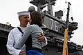US Navy 090528-N-2344B-078 Air Traffic Controller 3rd Class Andrew Lundeen kisses wife good-bye in front of the aircraft carrier USS Ronald Reagan (CVN 76).jpg