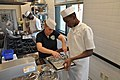 US Navy 110929-N-SQ684-078 Culinary Specialist 1st Class Helen Speight, from Hawthorne, Calif., helps Seaman Recruit Anthony Hicks, from Oakland, C.jpg