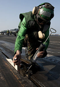 US Navy 120111-N-OY799-065 Aviation Boatswain's Mate (Equipment) Airman Krzysztof Urbanik greases the catapult shuttle on the flight deck of the Ni.jpg