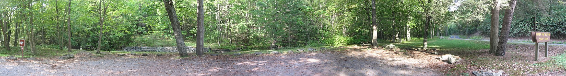 "A gravel lot surrounded by grass, large rocks and some large trees is in the foreground, with two picnic tables, the banks of a small stream and dense forest in the background. At the left is a sign reading ""Carry in, carry out"" and at right is a sign reading ""Upper Pine Bottom State Park"" with a two-lane highway behind it."