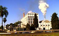 Foto de pli mallonga konstruaĵo kun fumo venanta for el fumtubo plej proksime al kvin-etaĝa oficeja konstruaĵo