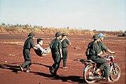 VC carrying POW in litter DD-ST-99-04295