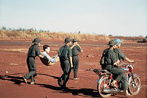 Viet Cong soldiers carry a litter with injured...