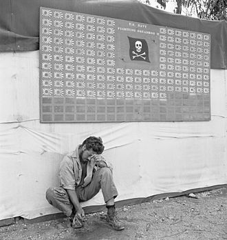 "VF-61 - ""Tired member of VF-17 pauses under the squadron scoreboard at Bougainville"" February 1944"