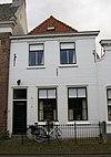 foto van Huis onder schilddak en met gebosseerd gepleisterde lijstgevel waarin twee lelie-ankers